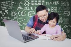 Studentessa che studia con l'insegnante nella classe Fotografia Stock