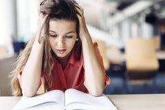 Studentessa che studia nella biblioteca Immagini Stock Libere da Diritti