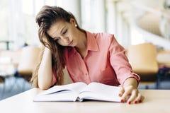 Studentessa che studia nella biblioteca Fotografie Stock Libere da Diritti