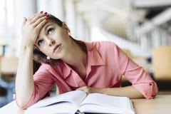 Studentessa che studia nella biblioteca Immagine Stock