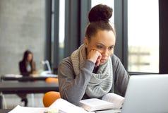 Studentessa che studia nella biblioteca con un computer portatile Fotografia Stock