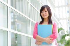 Studentessa cinese asiatica dell'istituto universitario con il fondo della città universitaria Immagine Stock