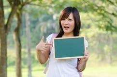 Studentessa cinese asiatica dell'istituto universitario con il fondo della città universitaria Immagini Stock Libere da Diritti