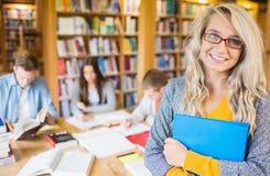 Studentessa con altre nel fondo alla biblioteca Fotografia Stock