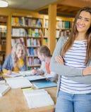 Studentessa con altre nel fondo alla biblioteca Immagine Stock Libera da Diritti