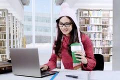 Studentessa con cioccolata calda in biblioteca Fotografie Stock