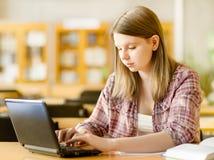 Studentessa con funzionamento del computer portatile Fotografia Stock