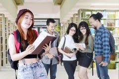 Studentessa con gli studenti pigri nella biblioteca Fotografie Stock