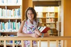 Studentessa con i libri che stanno nella biblioteca Immagini Stock Libere da Diritti