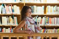 Studentessa con i libri che stanno nella biblioteca Fotografia Stock