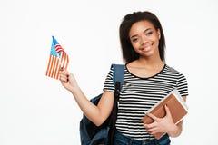 Studentessa con i libri della tenuta dello zaino e la bandiera degli Stati Uniti Immagine Stock Libera da Diritti