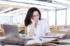Studentessa con i libri di lettura lunghi dei capelli nella classe Immagini Stock