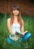 Studentessa con i libri su erba all'aperto Immagine Stock Libera da Diritti
