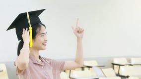 Studentessa con il cappello di graduazione in aula Fotografia Stock