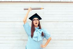 Studentessa con il cappello di graduazione che tiene una grande matita Fotografia Stock