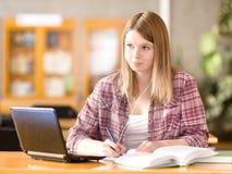 Studentessa con il computer portatile che funziona nella biblioteca Immagini Stock