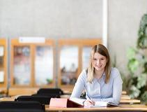 Studentessa con il computer portatile che funziona nella biblioteca Immagine Stock Libera da Diritti