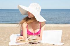 Studentessa con il computer portatile ed il libro bianchi sulla spiaggia Immagine Stock