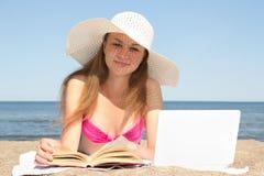 Studentessa con il computer portatile ed il libro sulla spiaggia Immagini Stock