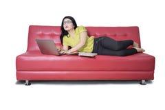 Studentessa con il libro facendo uso del computer portatile sul sofà Fotografia Stock Libera da Diritti