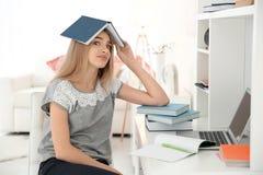 Studentessa con il libro sulla sua testa all'interno Immagini Stock