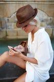 Studentessa con il sembrare alla moda che legge un messag del testo sul telefono delle cellule durante il viaggio di estate Immagine Stock