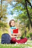 Studentessa con il taccuino che si siede su un'erba in un parco Immagine Stock Libera da Diritti