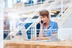 Studentessa con il telefono che lavora al computer portatile nello spazio moderno Fotografia Stock