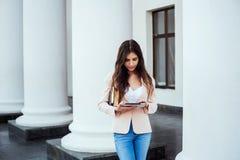 Studentessa con la compressa sulla città universitaria Immagine Stock