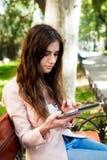 Studentessa con la compressa sulla città universitaria Fotografie Stock
