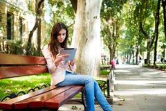 Studentessa con la compressa sulla città universitaria Fotografia Stock