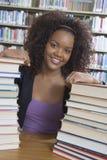 Studentessa con la pila di libri Fotografia Stock