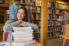 Studentessa con la pila di libri mentre altri nel fondo alla biblioteca Fotografie Stock