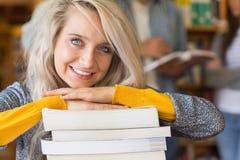 Studentessa con la pila di libri mentre altri nel fondo alla biblioteca Fotografia Stock Libera da Diritti