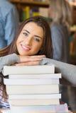 Studentessa con la pila di libri mentre altri nel fondo alla biblioteca Fotografie Stock Libere da Diritti