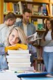 Studentessa con la pila di libri mentre altri nel fondo alla biblioteca Fotografia Stock