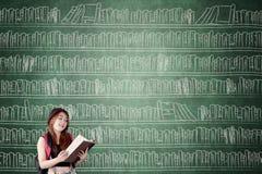 Studentessa con lo scaffale per libri sulla lavagna Immagine Stock Libera da Diritti