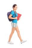 Studentessa con lo zaino che cammina e che tiene libro Fotografia Stock