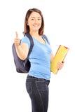 Studentessa con lo zaino che dà pollice su Immagini Stock Libere da Diritti