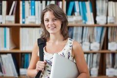 Studentessa contro lo scaffale per libri con il PC della compressa e borsa in biblioteca Fotografia Stock