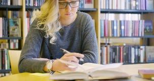 Studentessa dedicata con funzionamento di vetro nella biblioteca di scuola archivi video