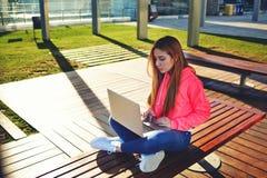 Studentessa dei capelli biondi che scrive sulla tastiera del computer portatile che si siede alla città universitaria Immagine Stock