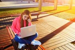 Studentessa dei capelli biondi messa a fuoco ed occupata facendo uso del computer portatile alla città universitaria Fotografie Stock Libere da Diritti