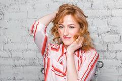 Studentessa del ritratto del primo piano bella giovane con capelli ricci e le lentiggini rossi sul suo fronte che si siede su un  fotografia stock
