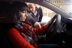 A studentessa dell'istruttore di guida mostrando come condurre un'automobile Fotografia Stock