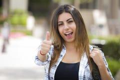 Studentessa della corsa mista sulla città universitaria della scuola con i pollici su Fotografia Stock Libera da Diritti