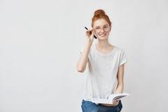 Studentessa della testarossa che sorride correggendo i vetri che tengono taccuino Immagini Stock Libere da Diritti