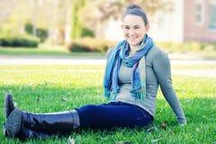 Studentessa di college che si siede sul prato inglese Fotografia Stock
