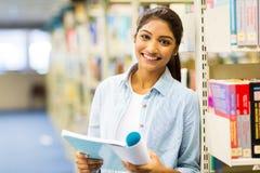 Studentessa di college indiana che legge un libro in biblioteca Fotografia Stock