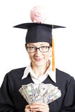 Studentessa di graduazione con gli occhiali che tengono i soldi a dei dollari Fotografia Stock Libera da Diritti